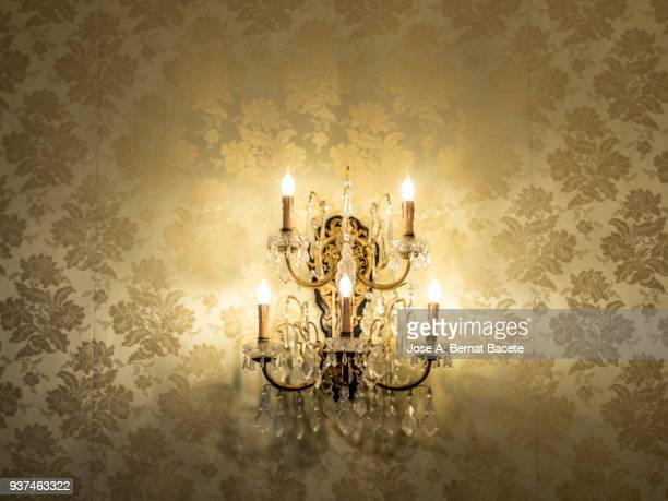 close-up of crystal wall lamp of classic style with the flushed lights on a wall with 	wallpaper. - ornaat stockfoto's en -beelden