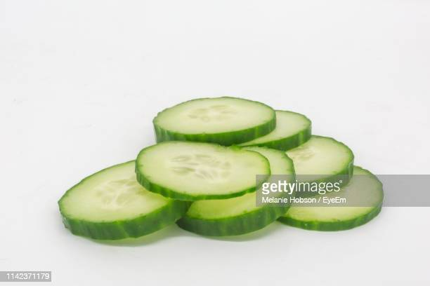 close-up of cucumber slices against white background - cucumber stock pictures, royalty-free photos & images