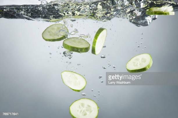 close-up of cucumber slices in splashing water - キュウリ ストックフォトと画像