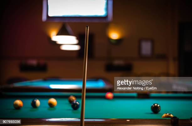Close-Up Of Cue By Pool Table