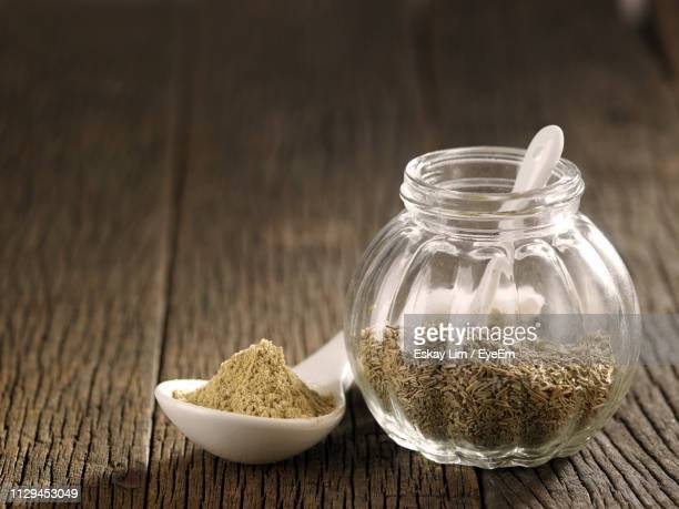 Close-Up Of Cumin Seeds In Glass Jar On Table