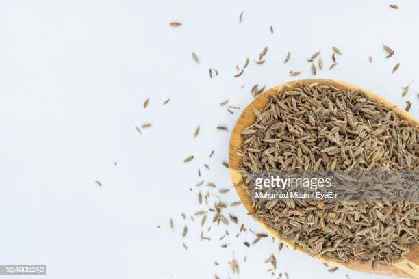 Close-Up Of Cumin Seeds In Wooden Spoon Over White Background