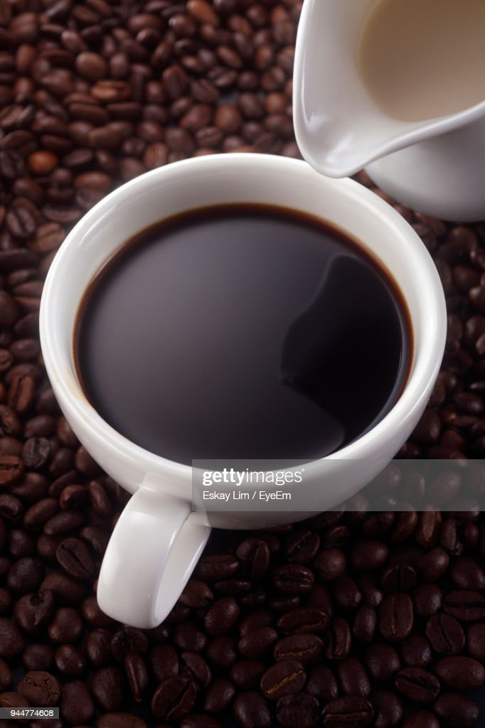 Close-Up Of Cup And Pot With Roasted Coffee Beans : Stock Photo