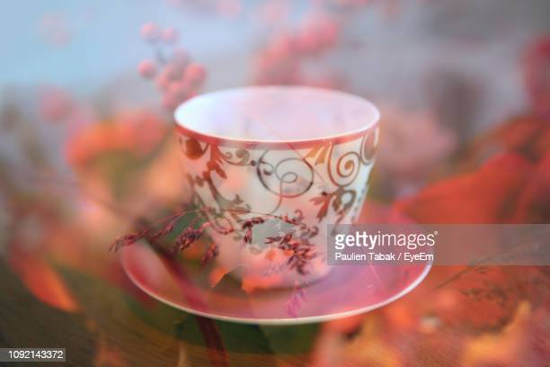 Close-Up Of Cup On Table Seen Through Glass