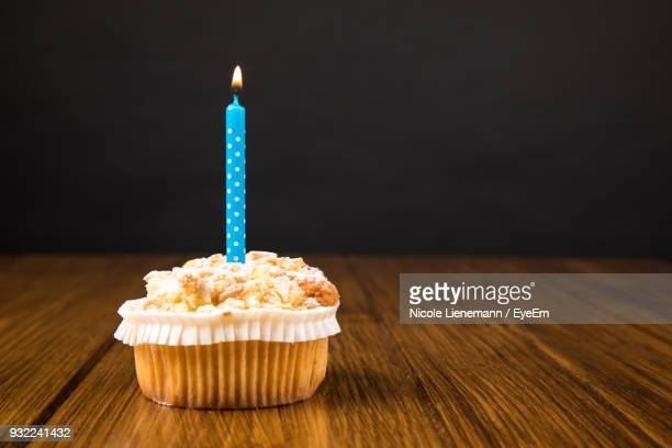 close-up of cupcakes on table against black background - birthday candles stock photos and pictures