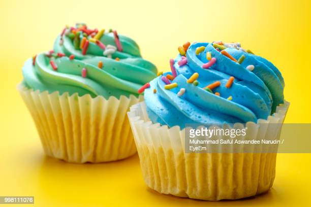 close-up of cupcakes over yellow background - icing stock pictures, royalty-free photos & images