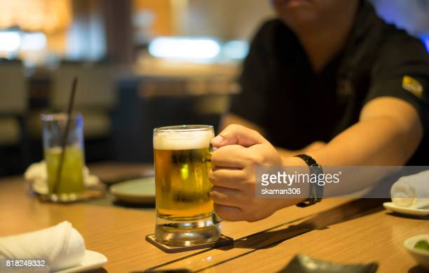 Close-up of  cups with beer glass out by business man using smart-phone after work