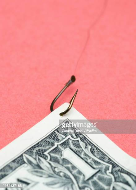 close-up of currency with hook on colored background - angelhaken stock-fotos und bilder