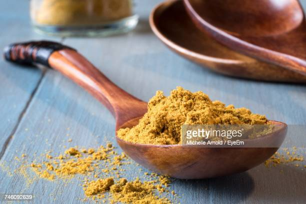 Close-Up Of Curry Powder In Wooden Spoon On Table