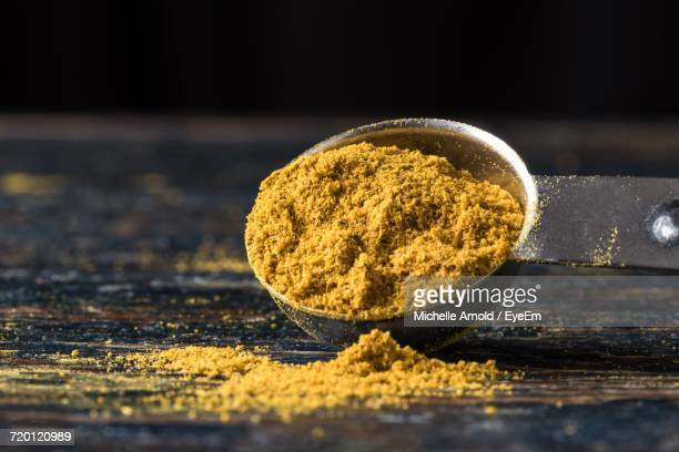 Close-Up Of Curry Powder Spilling From Measuring Spoon On Wooden Table
