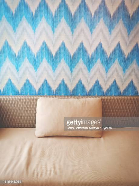 close-up of cushion on sofa against blue patterned wall at home - cushion stock pictures, royalty-free photos & images