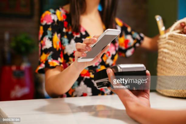 close-up of customer paying cashless with smartphone at counter of a store - partie du corps humain photos photos et images de collection