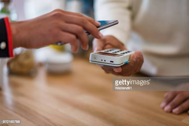 close-up of customer paying cashless with smartphone at counter of a store - bezahlen stock-fotos und bilder
