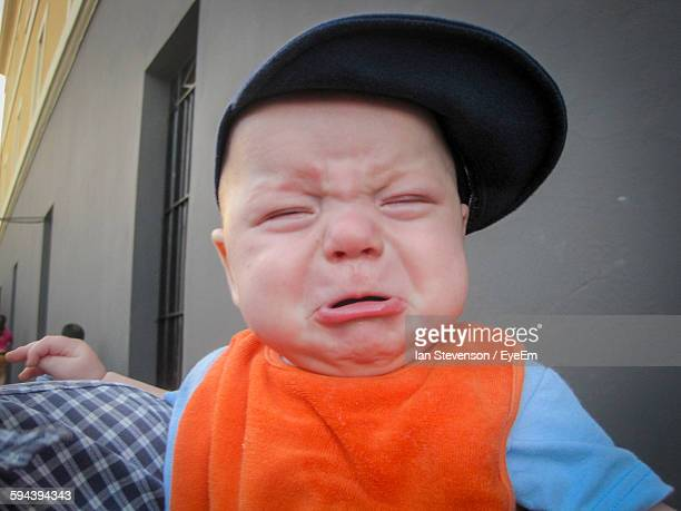 Close-Up Of Cute Baby Boy Crying Against Building