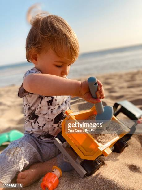 close-up of cute baby boy playing with toy and sand at beach - babyhood stock pictures, royalty-free photos & images