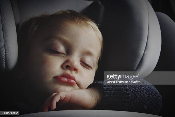 Close-Up Of Cute Baby Boy Sleeping On Car Seat