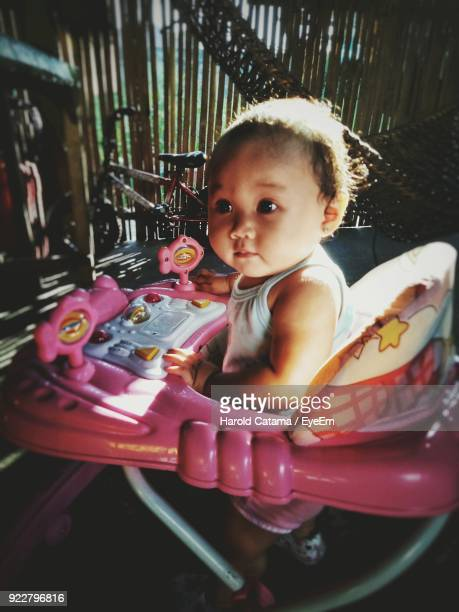 Close-Up Of Cute Baby Girl In Baby Walker