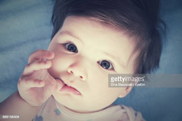 Close-Up Of Cute Baby Girl Lying On Bed