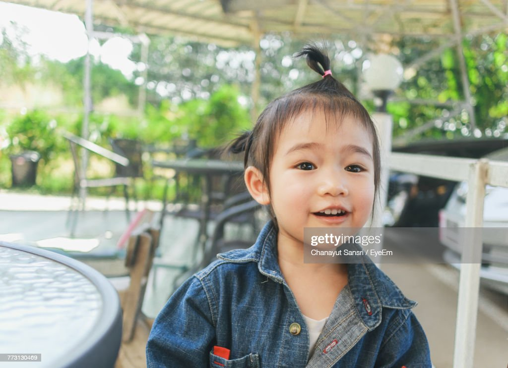 Close-Up Of Cute Baby Girl Sitting On Chair Outdoors : Photo