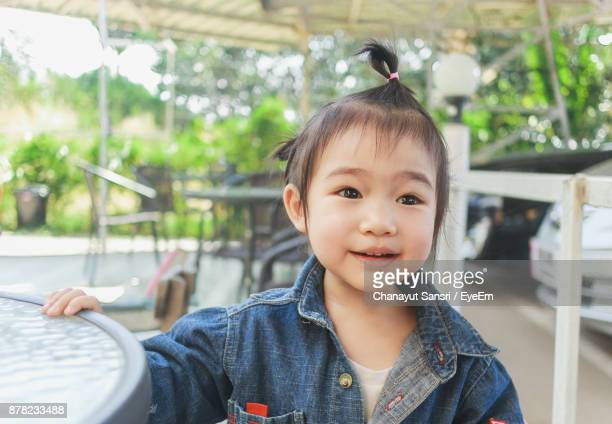 close-up of cute baby girl sitting on chair outdoors - chanayut stock photos and pictures