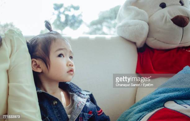 close-up of cute baby girl sitting on sofa at home - chanayut stock photos and pictures