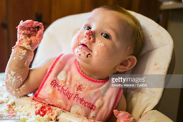 Close-Up Of Cute Baby Girl With Birthday Cake On Face At Home