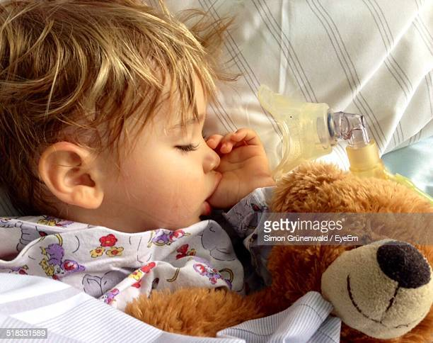 Close-up Of Cute Baby Sleeping In Bed With Teddy Bear