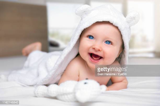 close-up of cute baby smiling while lying on bed - cute stock pictures, royalty-free photos & images