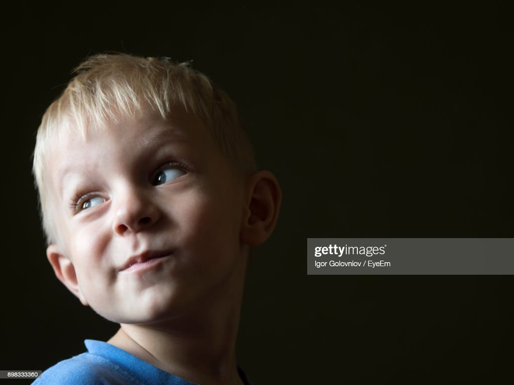 Close-Up Of Cute Boy Against Black Background : Stock Photo