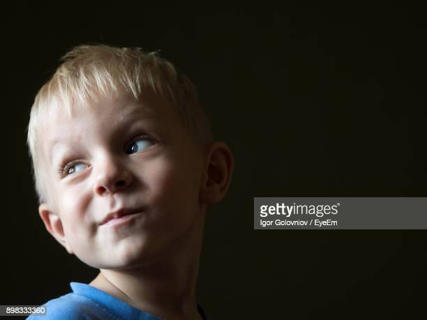 close-up of cute boy against black background - igor golovniov stock pictures, royalty-free photos & images