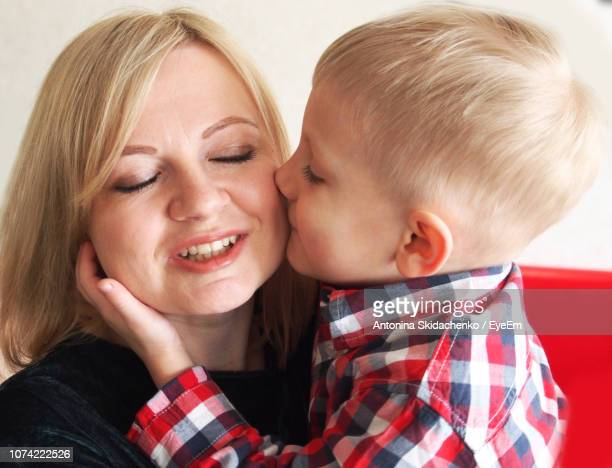 Close-Up Of Cute Boy Kissing Mother On Cheek At Home