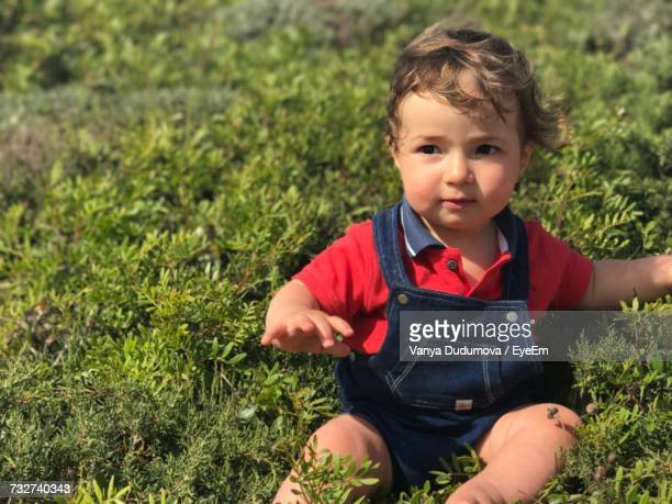 Close-Up Of Cute Boy Looking Away While Sitting On Grassy Field