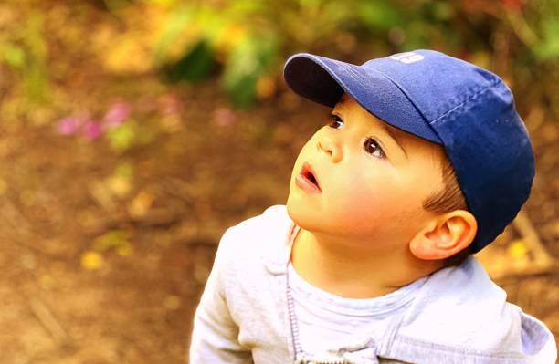 Close-Up Of Cute Boy Looking Away While Wearing Cap