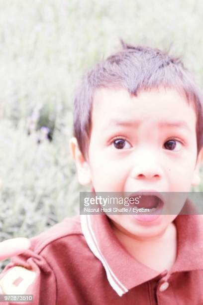Close-Up Of Cute Boy With Mouth Open Looking Away On Field