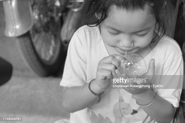 Close-Up Of Cute Girl Blowing Bubble While Sitting Outdoors