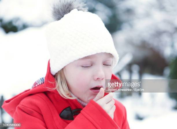 close-up of cute girl coughing during winter - coughing stock photos and pictures