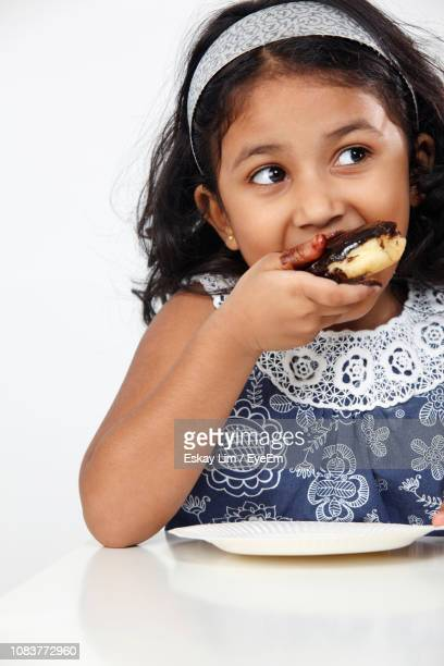 close-up of cute girl eating donut on table at home - one girl only stock pictures, royalty-free photos & images