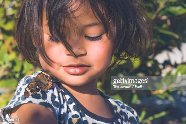 Close-Up Of Cute Girl Looking At A Butterfly