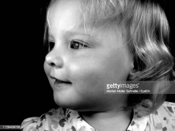 close-up of cute girl looking away against black background - morten müller schnelle stock-fotos und bilder