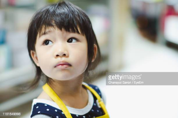 close-up of cute girl looking away at home - chanayut stock photos and pictures
