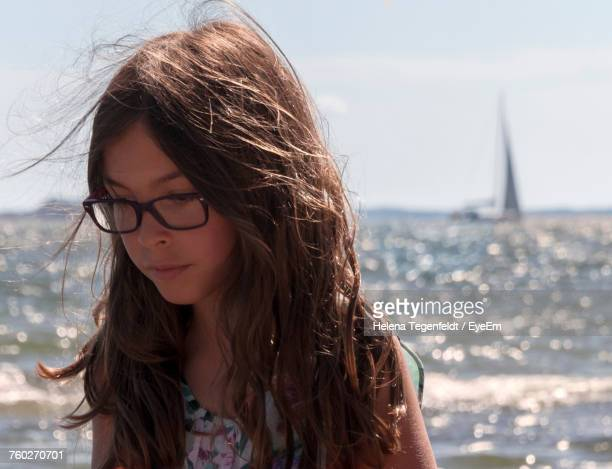 close-up of cute girl looking down against sea at beach - innocence stock pictures, royalty-free photos & images