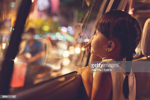 close-up of cute girl looking through car window at night - very young thai girls stock photos and pictures