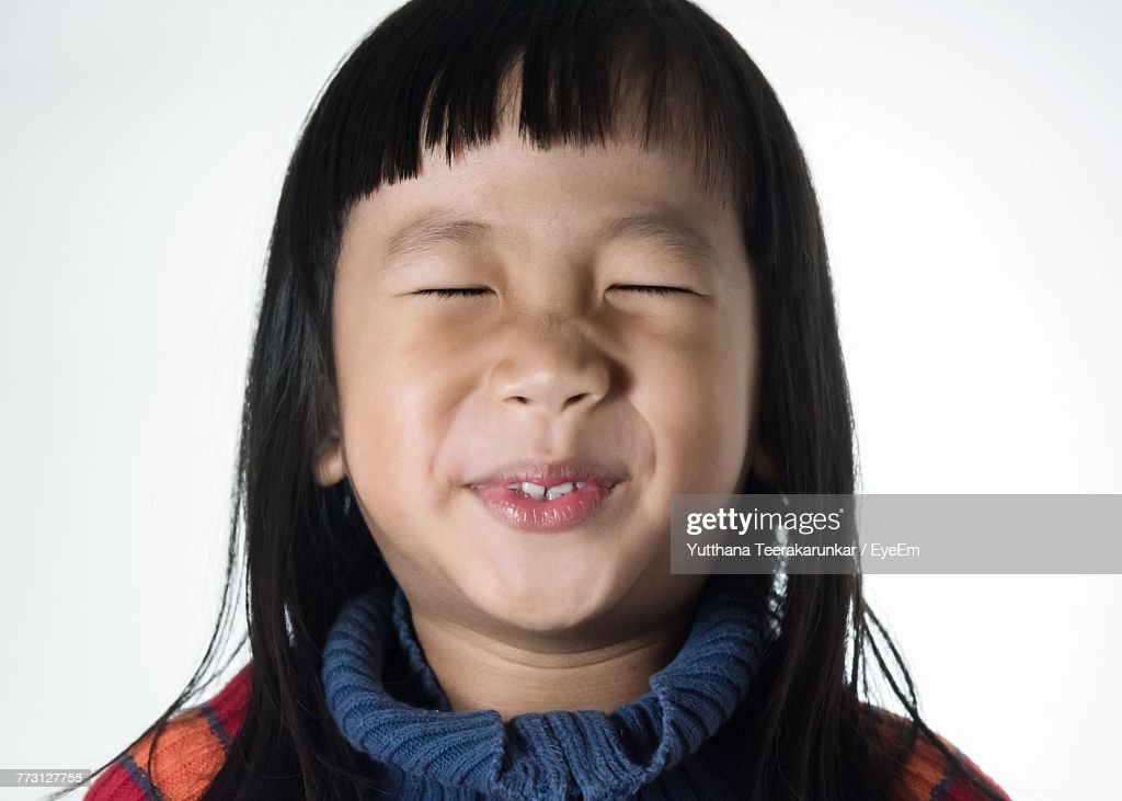 Close-Up Of Cute Girl Making Face Against White Background : Photo