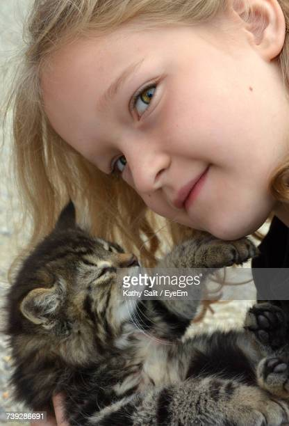 Close-Up Of Cute Girl Playing With Cat