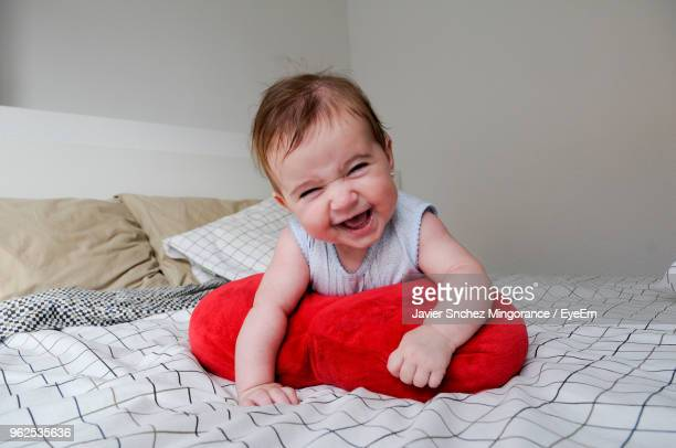 Close-Up Of Cute Girl Playing With Red Cushion On Bed At Home