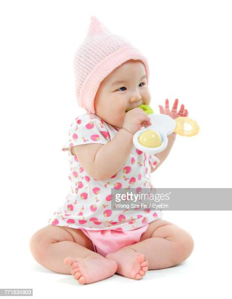 Close-Up Of Cute Girl Playing With Toy Against White Background