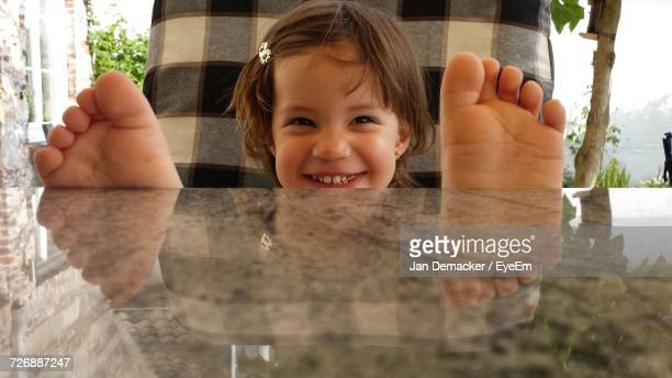 Close-Up Of Cute Girl Sitting On Chair With Feet Up On Table