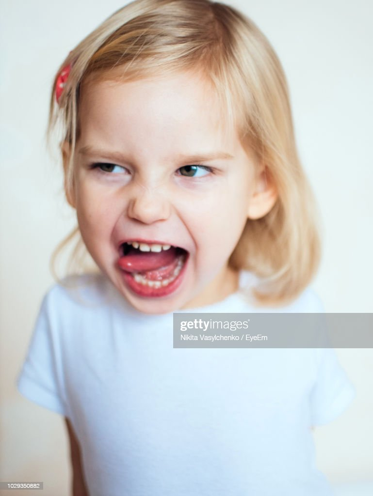 Closeup Of Cute Girl Sticking Out Tongue Against White