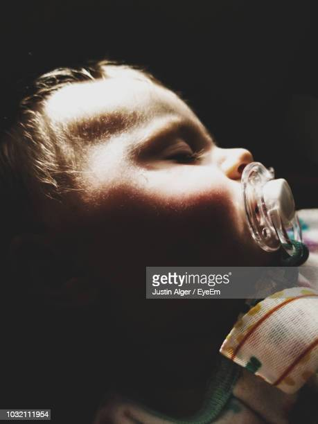 Close-Up Of Cute Girl Sucking Pacifier Against Black Background