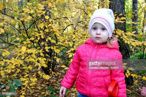 close-up of cute girl wearing pink jacket against plants at park - anastasi foto e immagini stock
